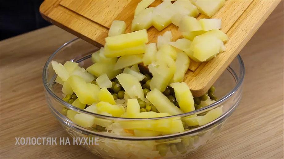 Добавление картофеля в салат с квашеной капустой и зеленым горошком
